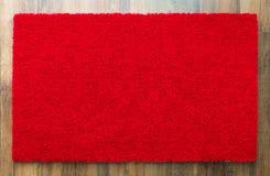 Recepción en blanco Mat On Wood Floor Background del rojo listo para su texto imagen de archivo