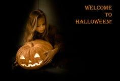 Recepción a Halloween muchacha con la calabaza que brilla intensamente en un fondo negro Foto de archivo libre de regalías