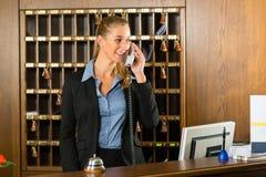 Recepción del hotel - empleado de mostrador que toma una llamada Foto de archivo libre de regalías