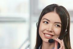 Recepcionista amistoso que sonríe y que lleva auriculares Foto de archivo