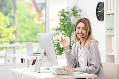 Recepcionista de sexo femenino con las auriculares en el escritorio Foto de archivo libre de regalías