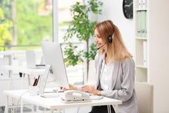 Recepcionista de sexo femenino con las auriculares en el escritorio Fotos de archivo libres de regalías