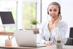Recepcionista de sexo femenino con las auriculares en el escritorio Imagen de archivo