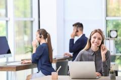 Recepcionista de sexo femenino con las auriculares en el escritorio Imagenes de archivo