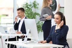Recepcionista de sexo femenino con las auriculares en el escritorio Foto de archivo