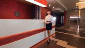 Recepcionista de sexo femenino encantador en pasillo del hotel