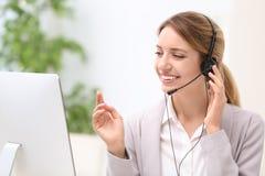 Recepcionista de sexo femenino joven con las auriculares Imagenes de archivo