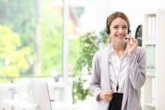 Recepcionista de sexo femenino joven con las auriculares Fotos de archivo libres de regalías