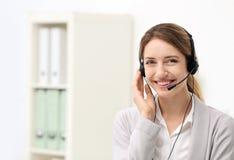 Recepcionista de sexo femenino joven con las auriculares en oficina Imagen de archivo libre de regalías