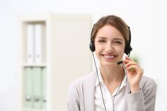 Recepcionista de sexo femenino joven con las auriculares en oficina Imágenes de archivo libres de regalías