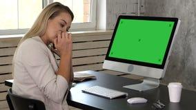 Recepcionista de sexo femenino joven que habla en el teléfono en oficina y que mira en monitor de su ordenador Maqueta verde de l almacen de video