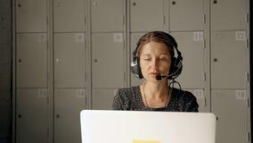 Recepcionista de sexo femenino que habla con el cliente en la línea directa almacen de metraje de vídeo