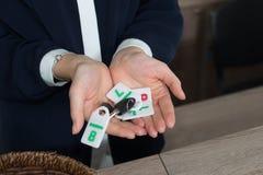 Recepcionista en la recepción del parador que muestra llaves con los dígitos a la huésped o al cliente imagenes de archivo