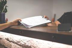 Recepcionista enviado os documentos ao convidado para assinar e encher-se acima do processo do registro do formulário Conceito do fotos de stock