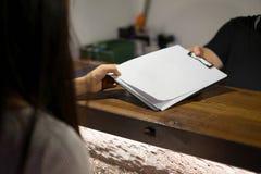 Recepcionista enviado os documentos ao convidado para assinar e encher-se acima do processo do registro do formulário Conceito do imagem de stock