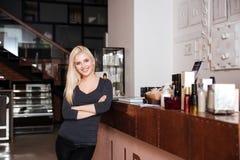Recepcionista fêmea do salão de beleza que está com as mãos cruzadas imagem de stock