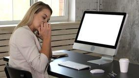 Recepcionista fêmea novo que fala no telefone no escritório e que olha no monitor de seu computador Indicador branco video estoque