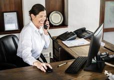 Recepcionista fêmea que trabalha na recepção foto de stock
