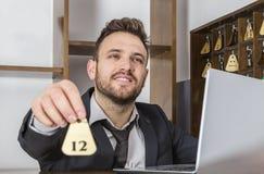 Recepcionista Giving la llave Foto de archivo