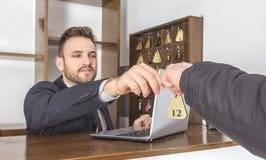 Recepcionista Giving la llave Fotografía de archivo