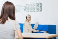 Recepcionista Looks At Woman no escritório do dentista Imagens de Stock Royalty Free
