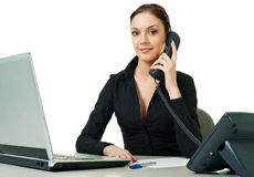 Recepcionista novo de sorriso que usa o telefone da mesa Fotografia de Stock