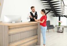 Recepcionista profesional que trabaja con el cliente en el escritorio en hotel imagen de archivo