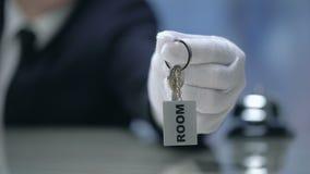 Recepcionista que dá as chaves de sala ao cliente, serviço de qualidade no hotel, registro filme