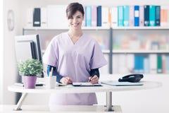 Recepcionista sonriente en la clínica imagenes de archivo