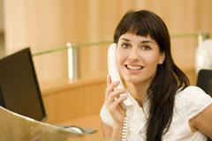 Recepionist atractive joven de la mujer con el teléfono imagenes de archivo
