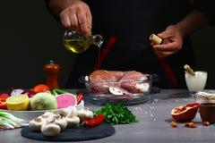 Recept för att laga mat kaninkött Hällande olja för kock på kaninkött, matlagningprocess, restaurangbegrepp arkivfoton