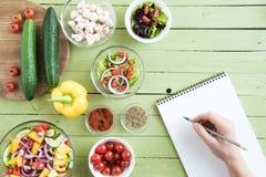 Recept för för personinnehavblyertspenna och handstil i kokbok, medan laga mat royaltyfria foton