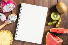 Receptanteckningsbok, drakefrukt, kiwi, vattenmelon, ananas på wo Royaltyfri Bild