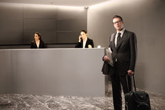 Reception. Businessman with suitcase with two receptionists on the background Royalty Free Stock Image