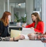 Reception agli ospiti dell'edificio per uffici che parlano con segretari Fotografia Stock