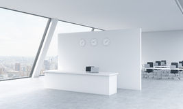 Reception area with clocks and workplaces in a bright modern open space loft office. White tables. New York panoramic view in the Royalty Free Stock Photography