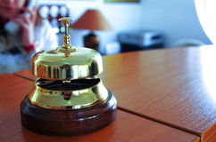 Reception bell. On hotel desk, receptionist speaking on the phone in the background royalty free stock photos