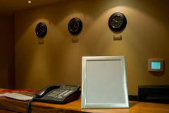 Reception desk with phone and row of clock Royalty Free Stock Images