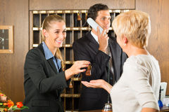 Reception - Guest checking in a hotel. At the front desk, the service is friendly Royalty Free Stock Photo