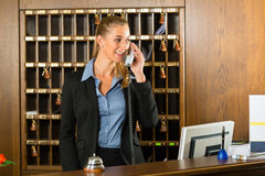 Reception of hotel - desk clerk taking a call Royalty Free Stock Photo