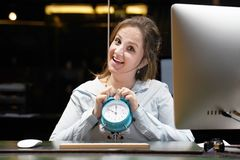 Reception in the hotel. Time management concept. Hotel administrator. A woman-reception worker holds an alarm clock in her hand in the workplace. Profile shot of stock photo