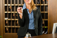 Reception of hotel - woman holding key in hand Royalty Free Stock Images
