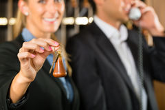 Reception in Hotel - woman with key. Reception in hotel - Man and woman standing at the front desk, man taking a call, woman holding a key in the hand and Royalty Free Stock Image