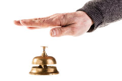 Reception. A mature old man ringing a hoted reception bell isolated over white Royalty Free Stock Images