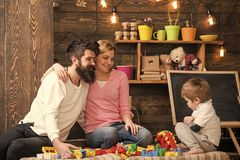 Reception parents. Kid with parents play with plastic blocks, build construction. Father, mother and cute son play with. Constructor bricks. Parenthood concept royalty free stock photo