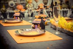 Reception table with a black tablecloth and decorations for halloween party, a small cardboard house, glasses and plates in carton. A Reception table with a royalty free stock image