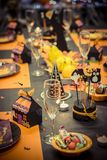 Reception table with halloween party decoration, glasses and candy plates stock images