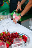 Reception table. Pour in wineglass. Glasses of wine, champagne, plates and berries on the white tablecloth. Catering business. Reception table. Glasses of wine Royalty Free Stock Photography