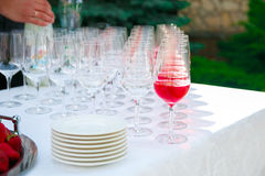 Reception table. Pour in wineglass. Glasses of wine, champagne, plates and berries on the white tablecloth. Catering business. Reception table. Glasses of wine Royalty Free Stock Photo