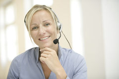 Receptionist. Woman with headphone smiling with blond hair, officesituation royalty free stock image